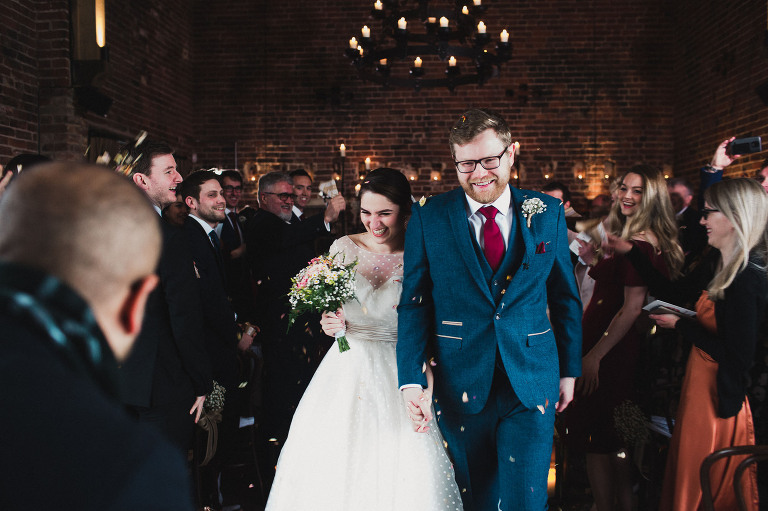bride and groom walk back down aisle as guests throw confetti