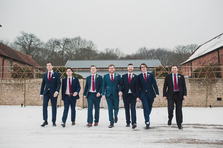 Groomsmen walking towards the camera, all wearing blue suits and red ties. All smiling