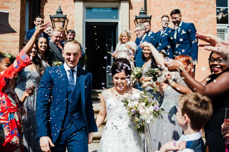 Bride and groom leaving The hotel being covered in confetti. Smiling happy faces
