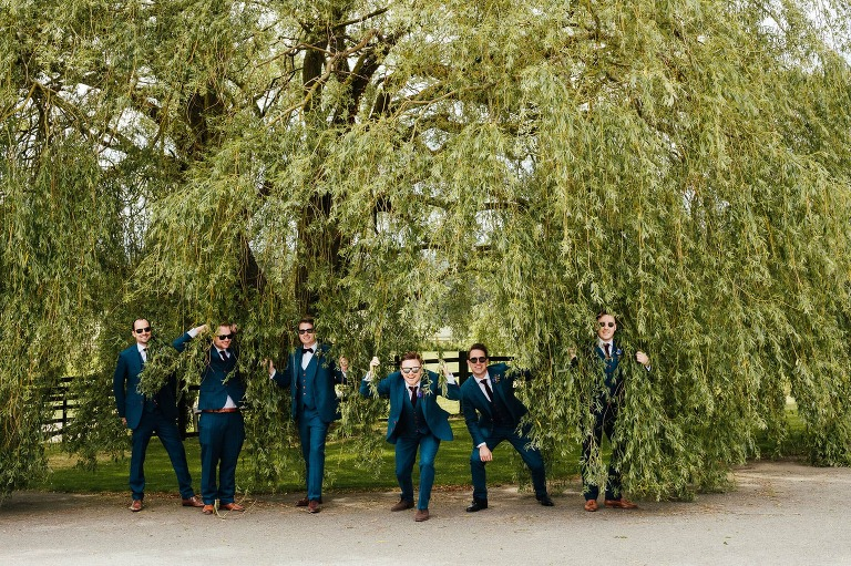 Crockwell Farm wedding photography - groomsmen peering through weeping willow