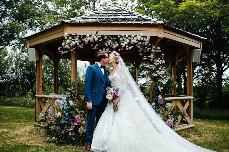 Crockwell Farm wedding Photography: Couple kiss in front of the pergola, adorned with flowers.