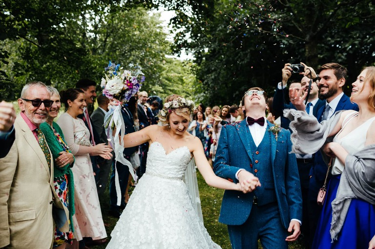 Crockwell Farm wedding Photography - bride and groom walking through confetti outside laughing