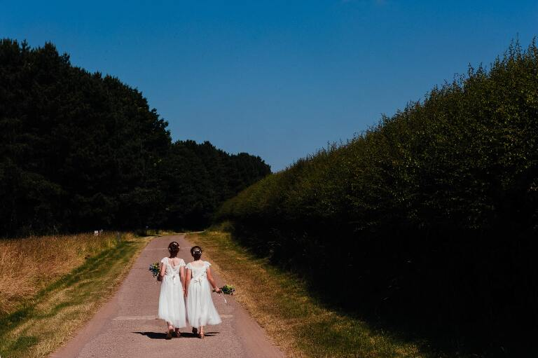 two flower girls walking off down the path hand in hand
