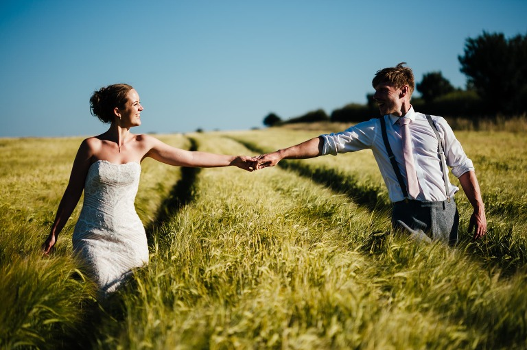 Bride and groom holding hands. Arms outstretched in a cornfield. Blue sky, looking at each other and smiling