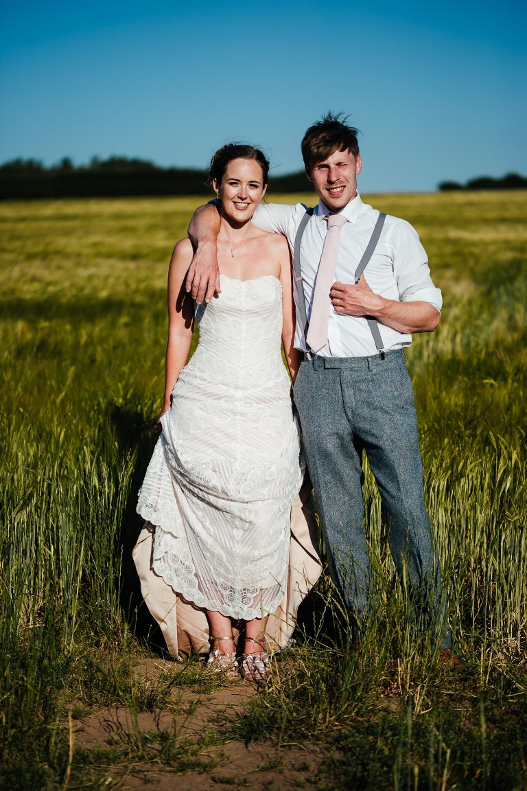 Bride and groom standing together in field facing camera. Bride lifting her dress just above her ankles. Groom with thumb tucked in his braces