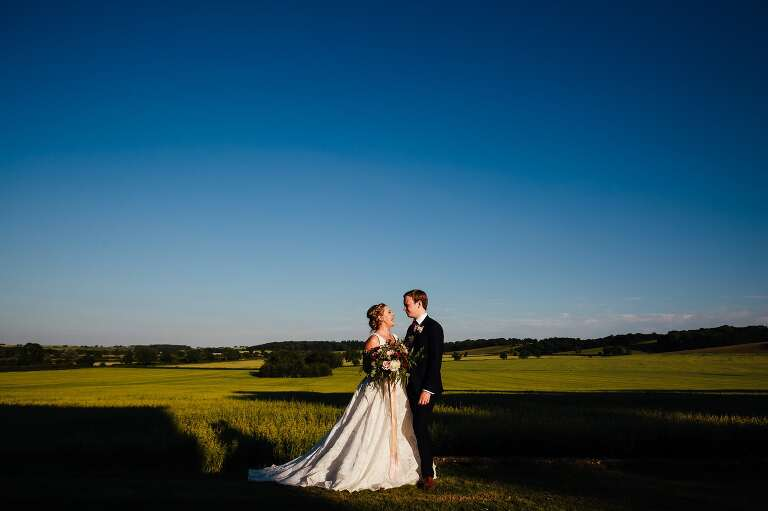Bride and groom staring in front of vista at Hothorpe Hall, lots of blue sky. laughing