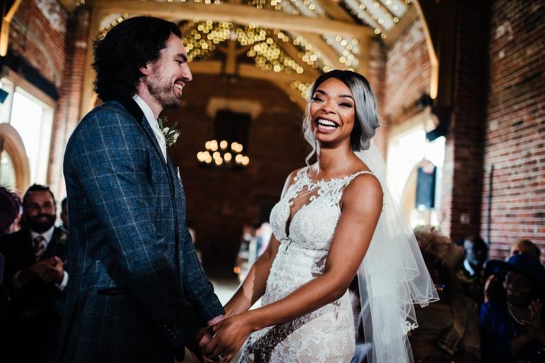 Barn weddings in Nottingham: Hazel gap barn wedding ceremony. Bride laughing, groom looking at bride.