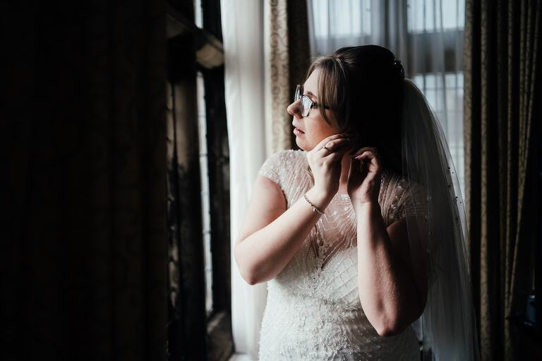 wedding photography at Breadsall Priory: Bride putting on earrings