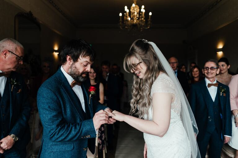 wedding photography at Breadsall Priory: bride and groom exchange rings