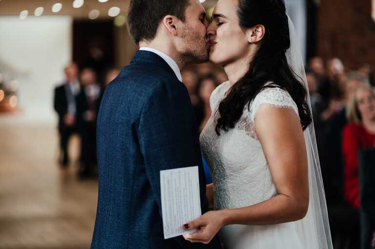 wedding photography at Carriage Hall. Bride and groom exchange first kiss