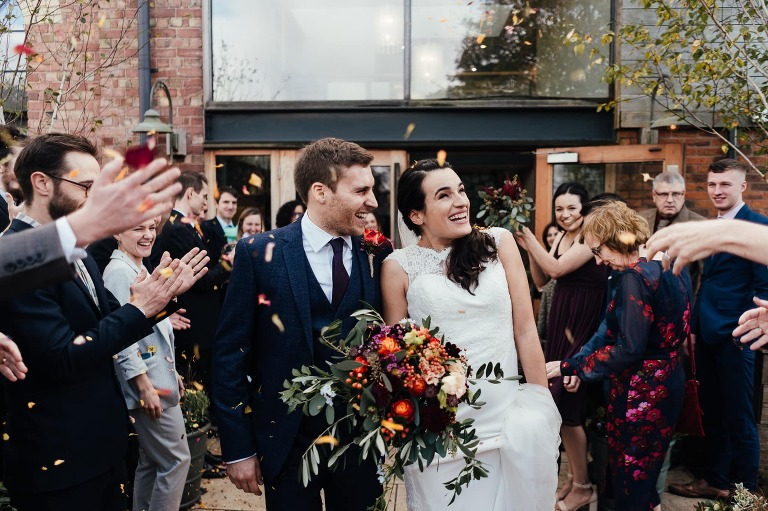 Wedding Photography at Carriage Hall - the couple walk out to confetti
