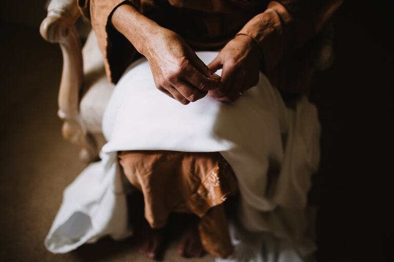 Wedding Photography at Talhenbont Hall - close up of mum sewing wedding dress