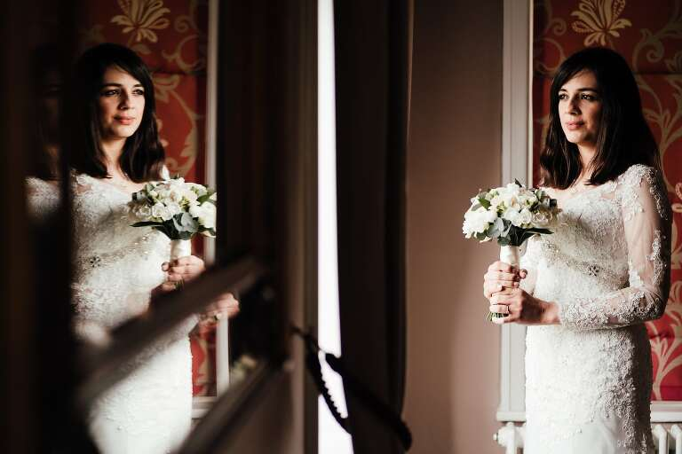 Wedding at West Bridgford Registry Office: Portrait of the bride in the window, reflected in the mirror too.