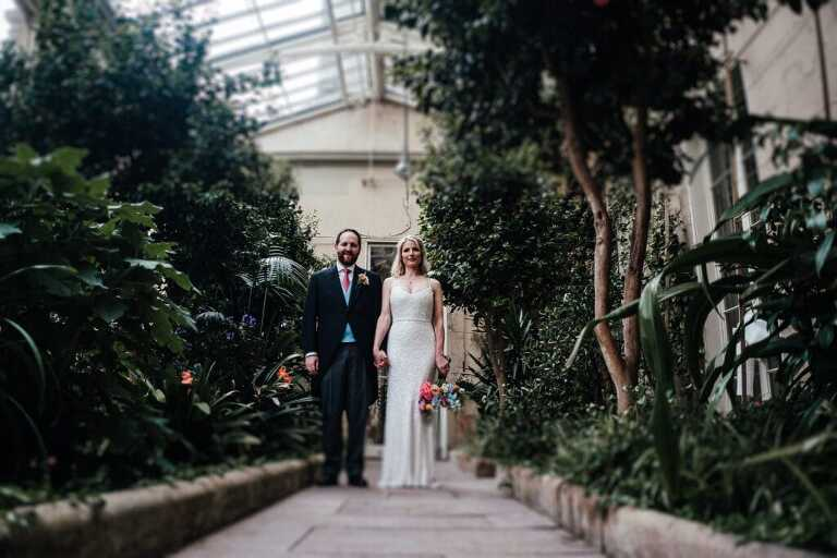 Bride and Groom standing in the Orangery at Prestwold Hall, facing the camera